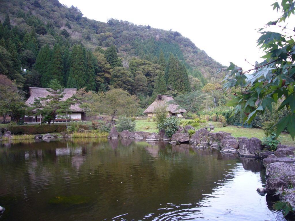 山と茅葺民家と池
